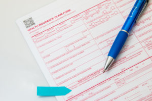 Health insurance claim form with pen on white background.