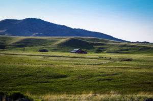 Landscape image of barn, cattle ranch, fence and hills