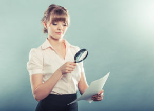 Woman uses magnifying glass to check paper